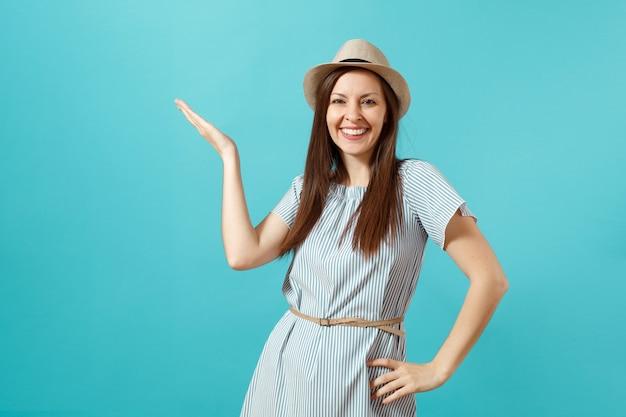 Ritratto di sorridente felice giovane donna elegante vestito da portare, cappello estivo di paglia che punta la mano da parte sullo spazio copia isolato su sfondo blu. concetto di stile di vita di emozioni sincere della gente. area pubblicitaria