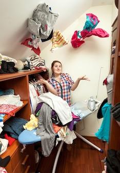 Ritratto di casalinga sorridente nello spogliatoio con vestiti che volano intorno