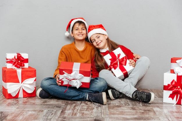 Ritratto di sorridente ragazzino e ragazza in cappelli di babbo natale con scatole regalo