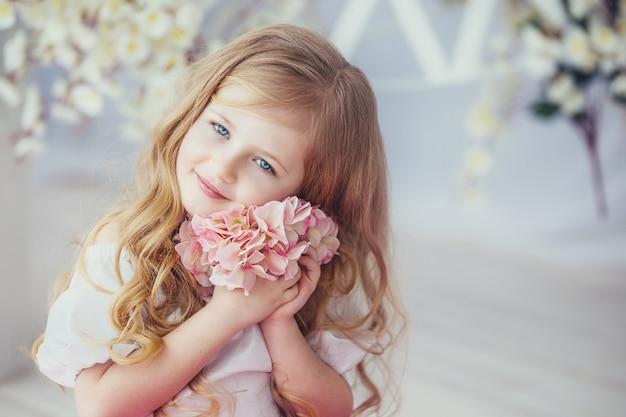 Ritratto di una bambina sorridente in vestito bello che si siede su un pavimento di legno chiaro