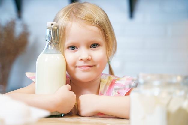 Ritratto di una bambina sorridente che tiene una bottiglia di latte in cucina.