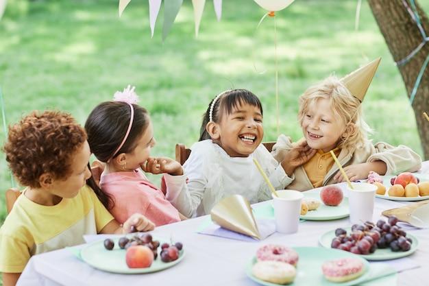 Ritratto di bambina sorridente con gli amici al tavolo da picnic all'aperto godendo la festa di compleanno in estate