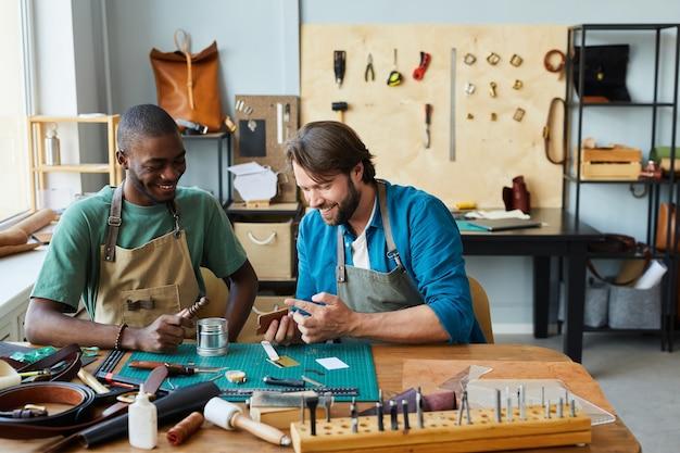 Ritratto di un artigiano maschio sorridente che insegna a un giovane apprendista nello spazio della copia dell'officina dei pellettieri