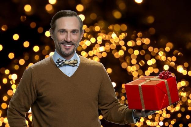 Ritratto dell'uomo sorridente che tiene il contenitore di regalo rosso. positivo affascinante maturo uomo caucasico con regalo di natale su sfondo con luci incandescenti.