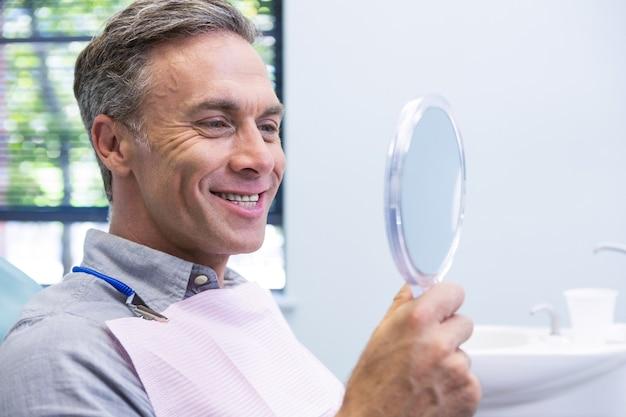 Ritratto dell'uomo sorridente che osserva in specchio