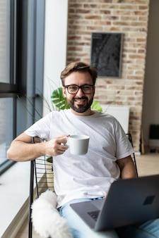 Ritratto di un uomo sorridente che si rilassa sulla sedia vicino alla finestra facendo uso del computer portatile e tenendo la tazza di caffè a casa