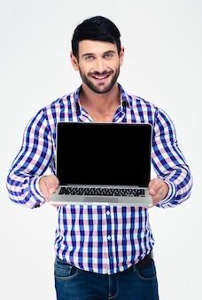Ritratto di un uomo sorridente che mostra lo schermo del computer portatile in bianco isolato su un muro bianco