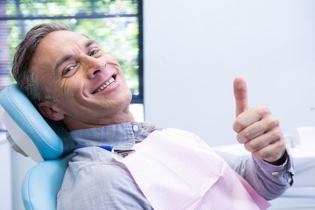 Ritratto dell'uomo sorridente che mostra i pollici