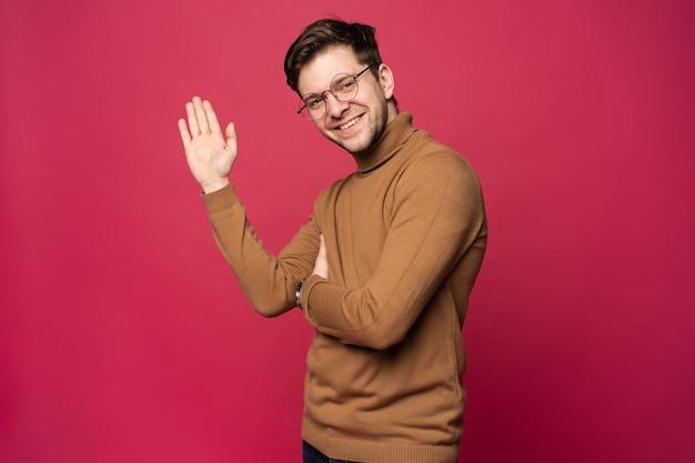 Ritratto di uomo sorridente con la mano alzata in segno di saluto. batti il cinque concetto