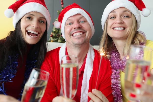 Ritratto di uomo e donna sorridenti con un bicchiere di champagne e cappelli di babbo natale