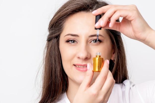 Il ritratto del maestro sorridente del manicure tiene la bottiglia dello smalto per unghie dell'oro
