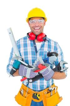Ritratto del lavoratore manuale sorridente che tiene i vari strumenti