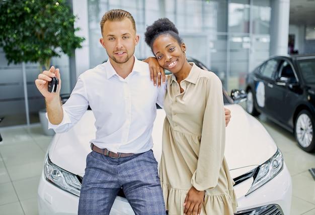 Ritratto della coppia sposata sorridente con le chiavi dalla loro nuova automobile