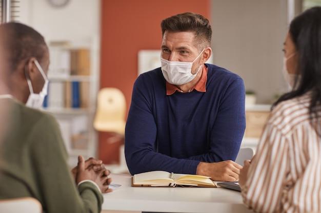 Ritratto di sorridente uomo d'affari maturo che indossa la maschera durante la riunione di lavoro in ufficio, copia dello spazio