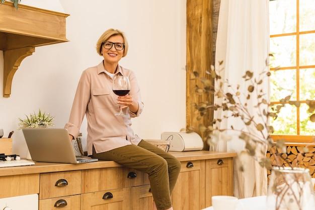 Ritratto di donna anziana matura sorridente che tiene in mano un bicchiere di vino mentre si utilizza il computer portatile sul tavolo della cucina. freelance che lavora a casa concetto.