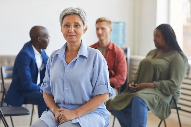 Ritratto di donna matura sorridente durante la riunione del gruppo di supporto con persone sedute in cerchio, copia dello spazio