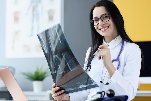 Ritratto della donna sorridente del medico che tiene l'immagine dei raggi x. concetto di servizi medici