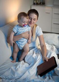 Ritratto di madre sorridente e adorabile libro di lettura del bambino prima di andare a dormire