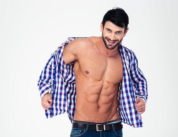 Ritratto di un uomo muscoloso sorridente che spoglia la camicia isolata su un muro bianco