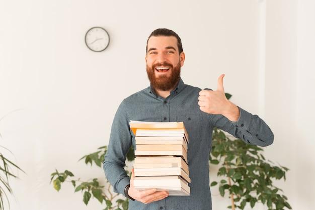 Ritratto di impiegato sorridente che tiene molti libri e che mostra il pollice in su