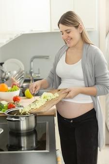 Ritratto di donna incinta sorridente che mette le verdure nella zuppa