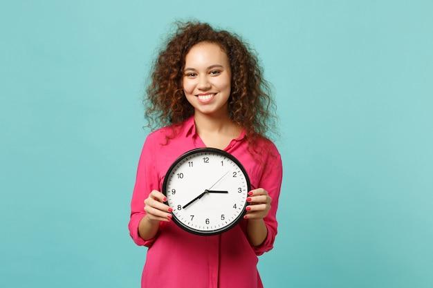Ritratto della ragazza abbastanza africana sorridente in vestiti casuali rosa che tengono orologio rotondo isolato sul fondo blu della parete del turchese in studio. persone sincere emozioni, concetto di stile di vita. mock up copia spazio.