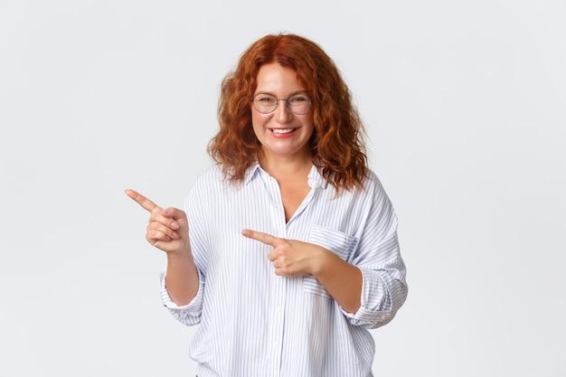 Ritratto di sorridente donna di mezza età piuttosto con i capelli rossi, con gli occhiali, mostrando la strada, aiutando con la scelta, dimostrando banner promozionale e guardando soddisfatto, in piedi muro bianco.