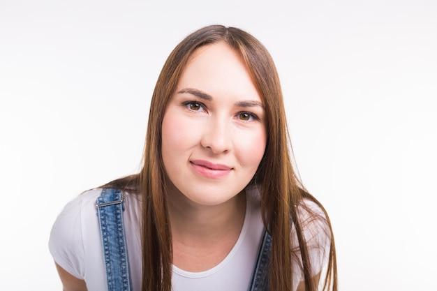Ritratto di una donna graziosa sorridente in denim globale isolato sul muro bianco