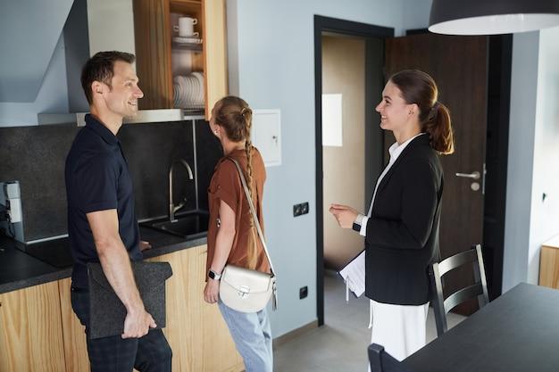 Ritratto di un agente immobiliare sorridente che mostra casa a una giovane coppia che acquista proprietà, copia spazio