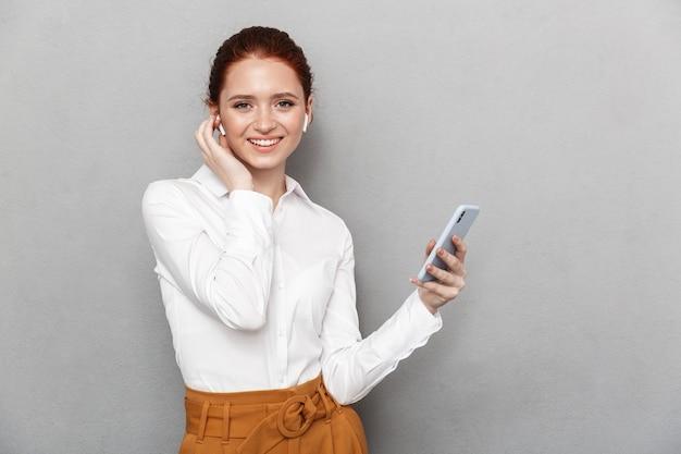 Ritratto di sorridente imprenditrice rossa 20s indossando auricolari tenendo e guardando lo smartphone in ufficio isolato su gray