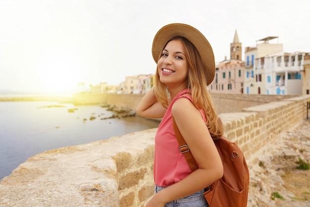 Ritratto di sorridente viaggiatore rilassato donna camminando lungo il lungomare di alghero, sardegna, italy