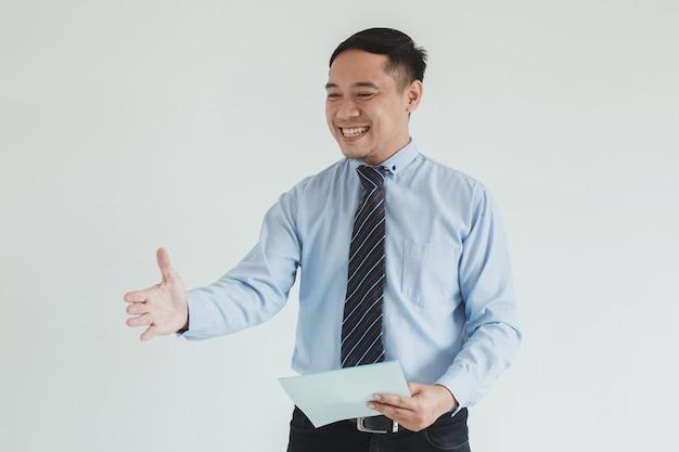 Ritratto di un addetto alle vendite sorridente che indossa una camicia blu e una cravatta che allunga la mano per stringere la mano nello spazio vuoto mentre tiene carta bianca