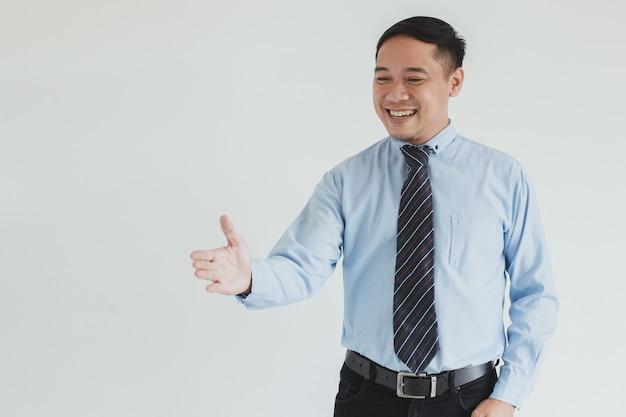 Ritratto di un addetto alle vendite sorridente che indossa camicia blu e cravatta che allunga la mano per stringere la mano nello spazio vuoto