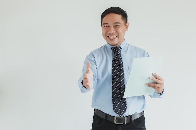 Ritratto di un addetto alle vendite sorridente che indossa camicia blu e cravatta che allunga la mano per stringere la mano mentre tiene carta bianca alla telecamera