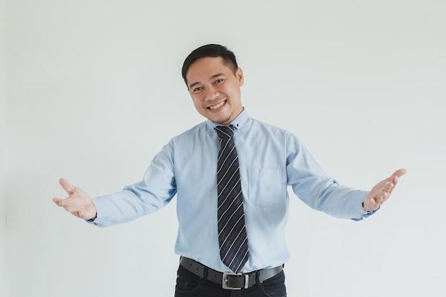 Ritratto di un addetto alle vendite sorridente che indossa camicia e cravatta blu che saluta con un gesto di benvenuto e pronto per il servizio in telecamera