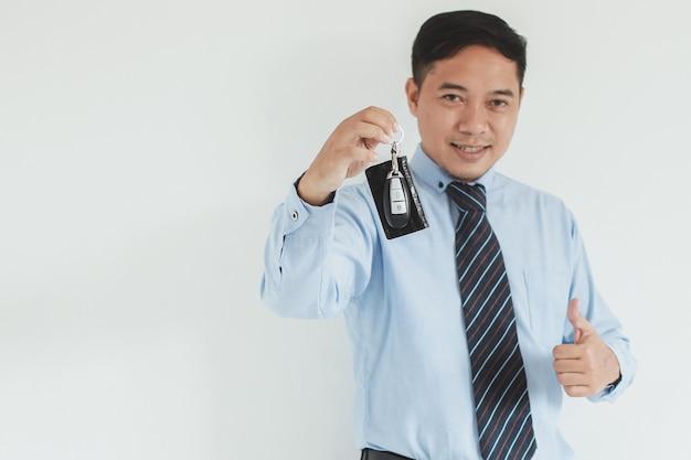 Ritratto di un uomo di vendita sorridente che indossa camicia e cravatta blu che dà una chiave dell'auto e pollice in su alla fotocamera con spazio per le copie