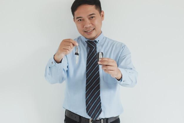 Ritratto di un addetto alle vendite sorridente che indossa camicia e cravatta blu che dà una chiave e un telecomando di controllo dell'allarme per l'auto alla telecamera