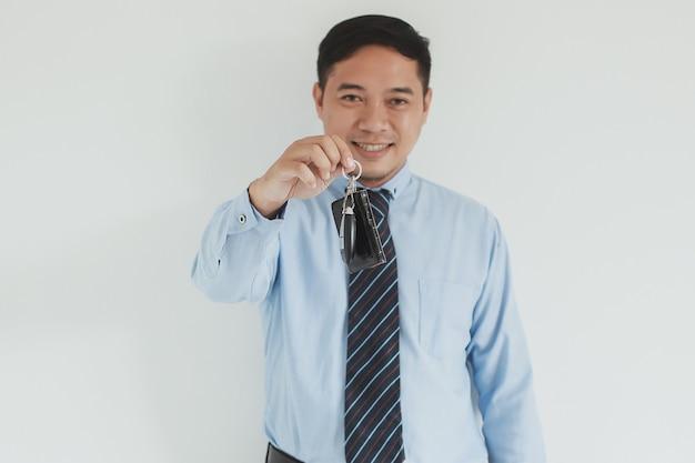 Ritratto di un addetto alle vendite sorridente che indossa camicia blu e cravatta che dà una chiave alla telecamera