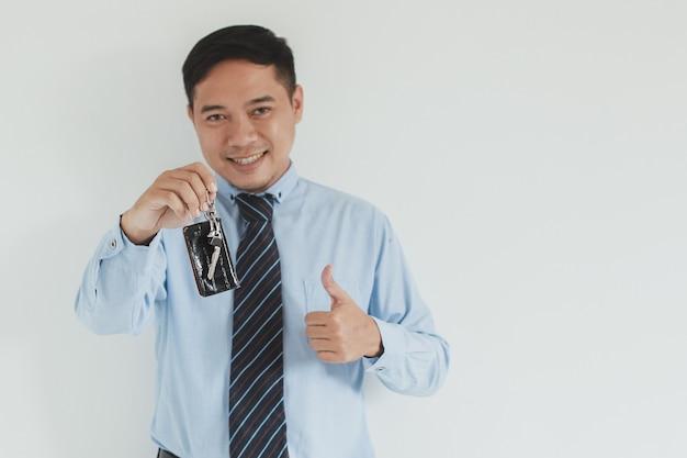 Ritratto di un addetto alle vendite sorridente che indossa camicia e cravatta blu con in mano la chiave dell'auto e il pollice in alto alla telecamera con spazio di copia