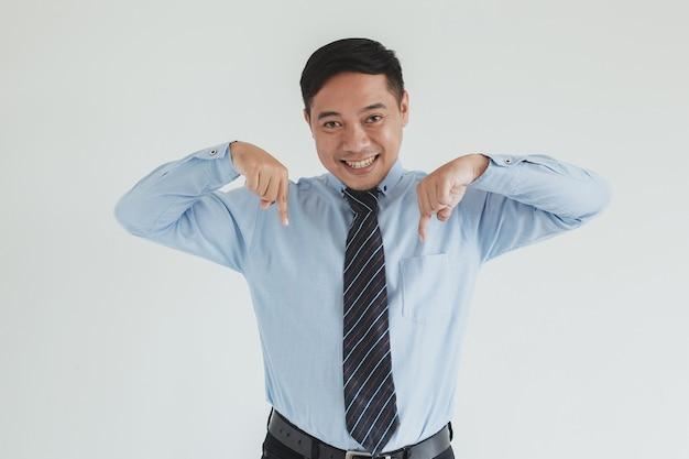 Ritratto di un addetto alle vendite sorridente che indossa camicia blu e cravatta rivolta verso il basso su uno spazio vuoto per la pubblicità