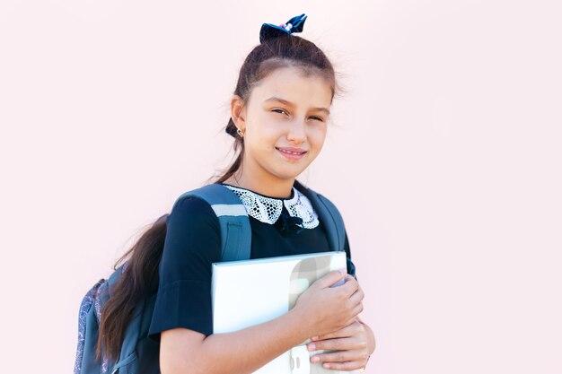 Ritratto di una ragazza sorridente della scuola sullo sfondo di colore rosa pastello.