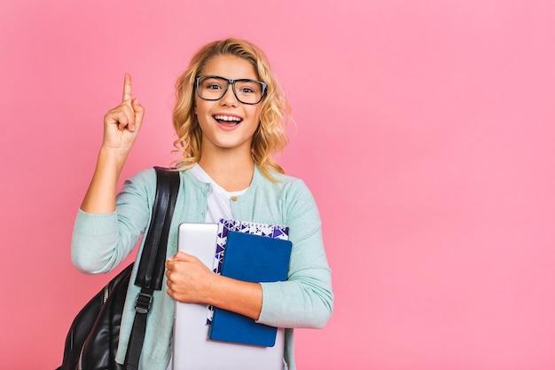 Ritratto del bambino sorridente della ragazza della scuola con la borsa, il laptop ed i libri di scuola