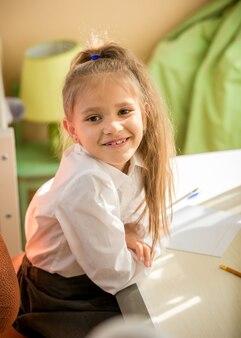 Ritratto di studentessa sorridente seduta alla scrivania in camera da letto