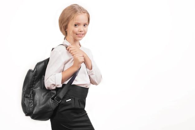 Ritratto di una studentessa sorridente in uniforme con lo zaino della scuola