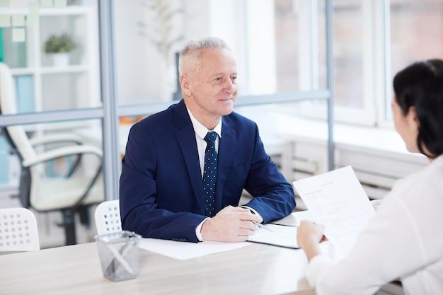 Ritratto dell'uomo d'affari maggiore sorridente che intervista giovane donna per posizione di lavoro in ufficio