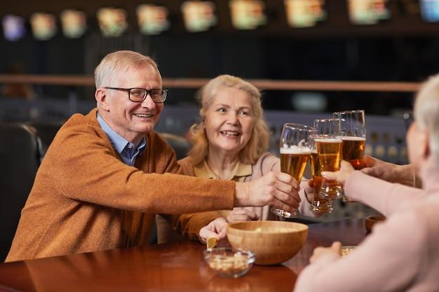 Ritratto di una coppia anziana sorridente che beve birra al bar e bicchieri tintinnanti mentre si gode la serata fuori con gli amici, copia spazio