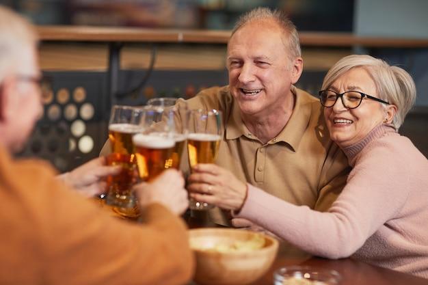 Ritratto di una coppia anziana sorridente che beve birra al bar e bicchieri tintinnanti mentre si gode la serata con gli amici