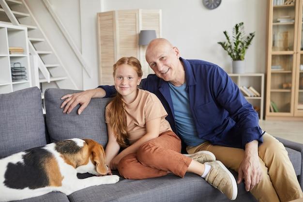 Ritratto di uomo anziano sorridente in posa con la nipote carina mentre era seduto sul divano in interni domestici accoglienti