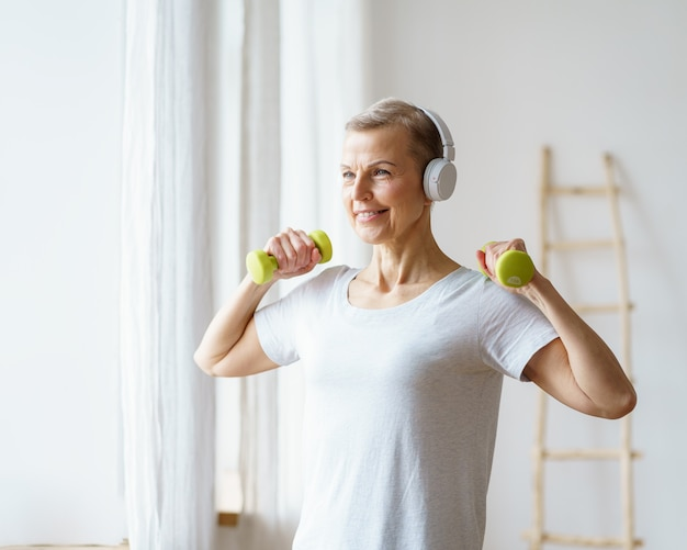 Ritratto di donna anziana sorridente che esercita fitness con manubri a casa