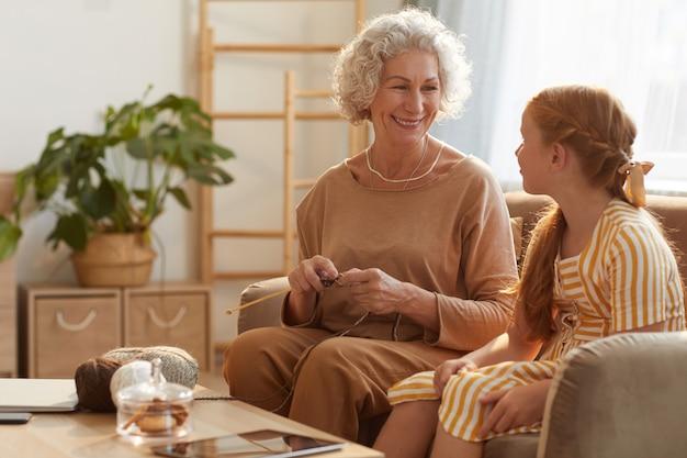 Ritratto di donna senior sorridente maglieria con ragazza carina guardandola in casa accogliente illuminata dalla luce del sole